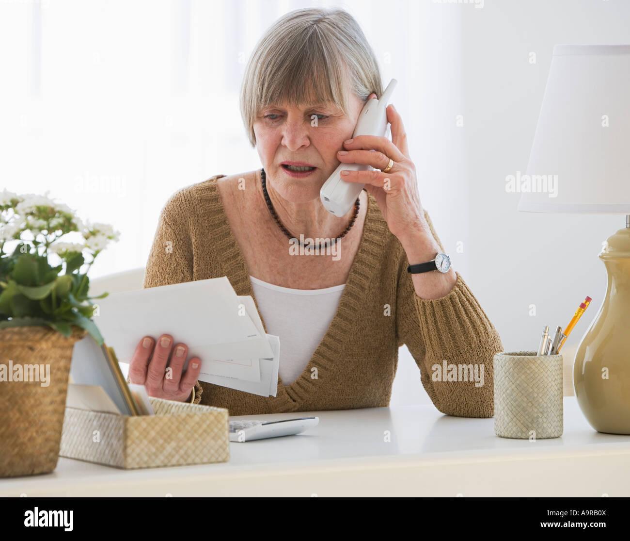 Senior donna guardando le bollette Immagini Stock