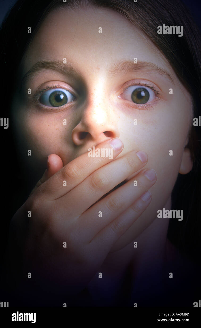 Ragazza giovane faccia dando aspetto di sorpresa con la mano nella parte anteriore della bocca Immagini Stock