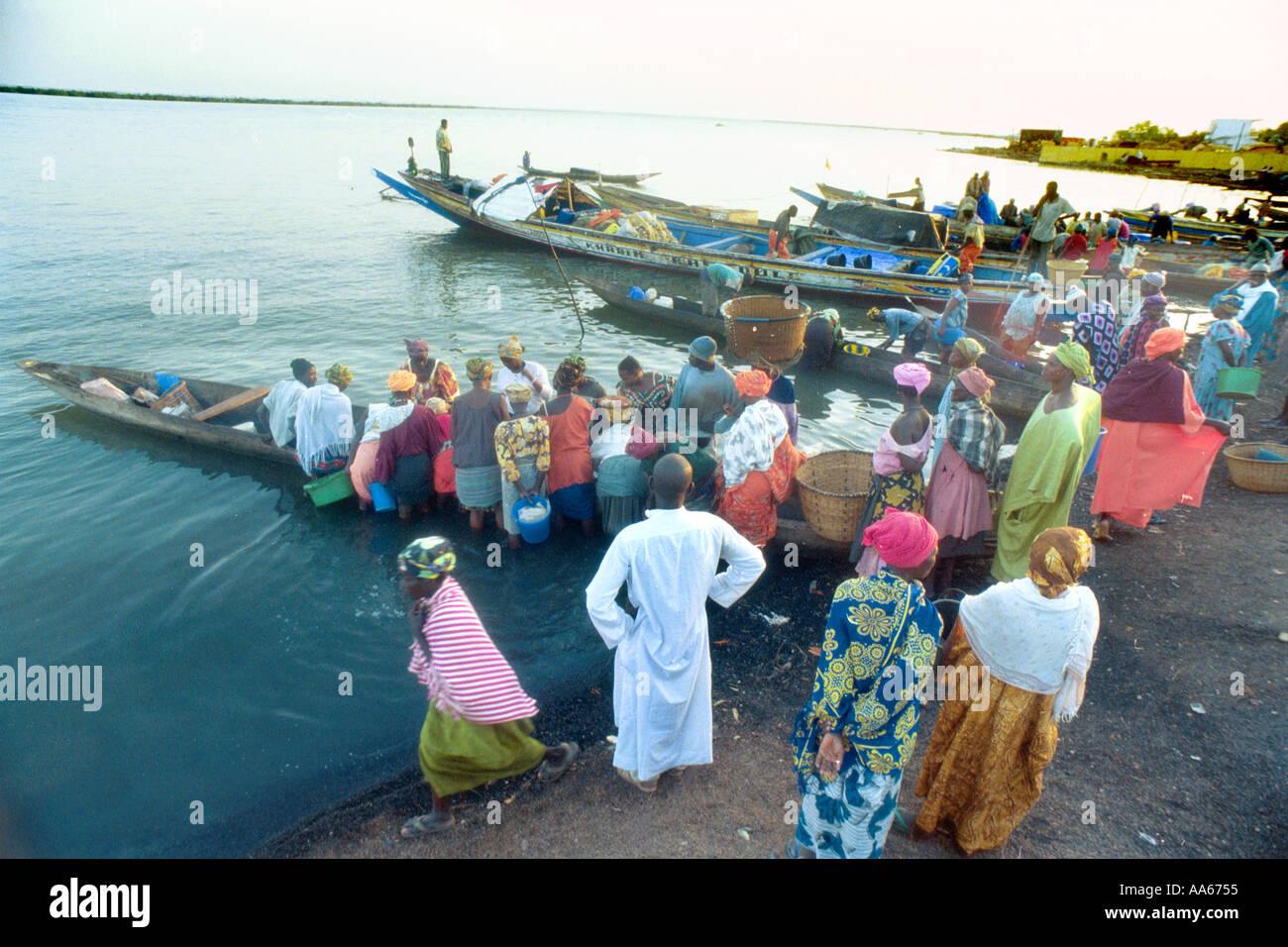 Commercianti senegalesi attendere per i pescatori locali per portare nei giorni dal raccolto di loro piccole piroghe in Occidente Arican city Immagini Stock