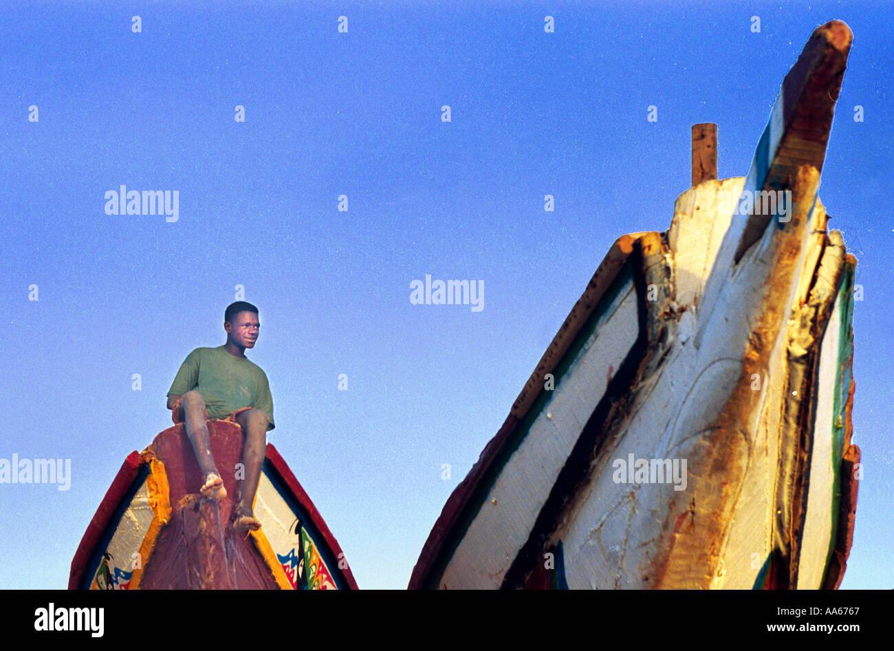 Un mauritano si siede su una delle numerose piroghe utilizzate da artigiani locali di pescatori sulla costa della Mauritania nei pressi della capitale Immagini Stock
