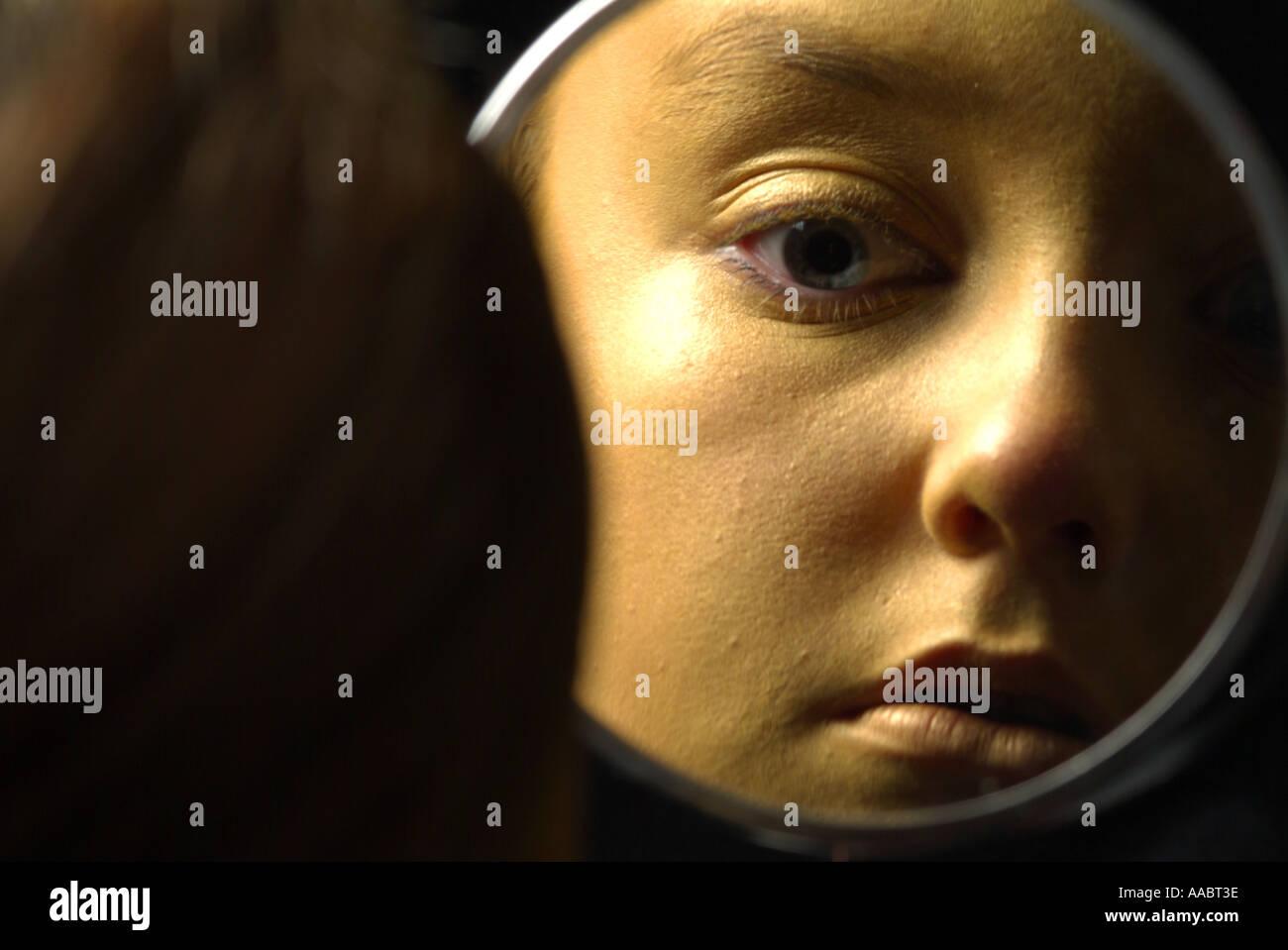 La faccia di oro ragazza guardando nello specchio Immagini Stock