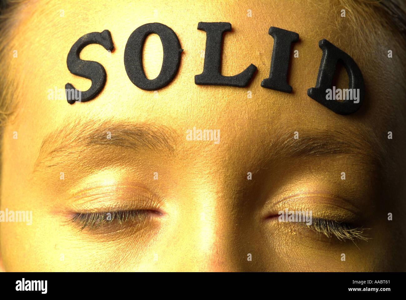 La faccia di oro oro ragazza faccia la ragazza con gli occhi aperti urlando centro di fronte solido scritte in oro Immagini Stock
