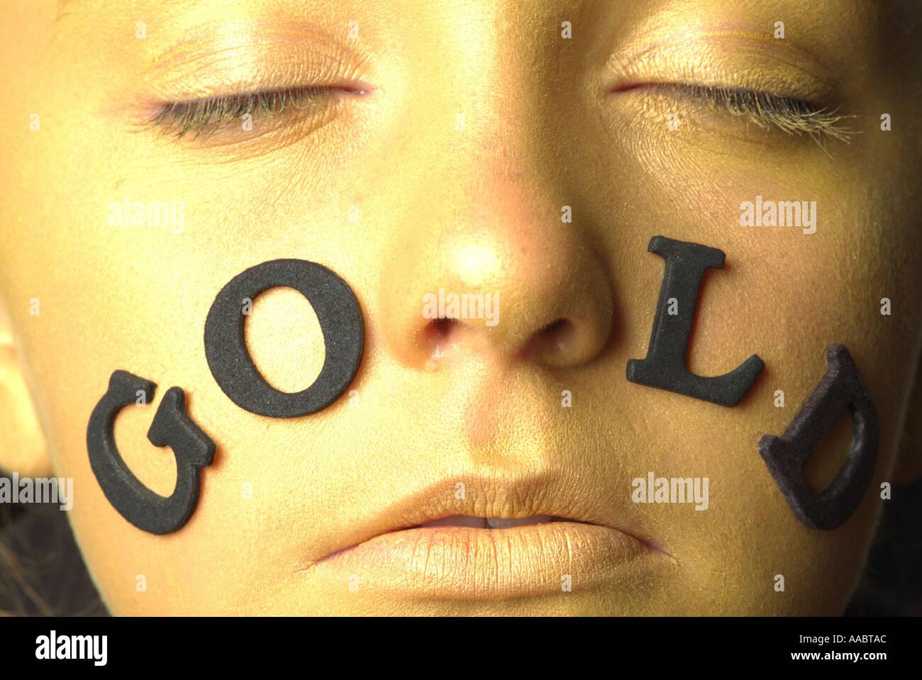 La faccia di oro ragazza closeup di occhi naso bocca con le scritte oro Immagini Stock
