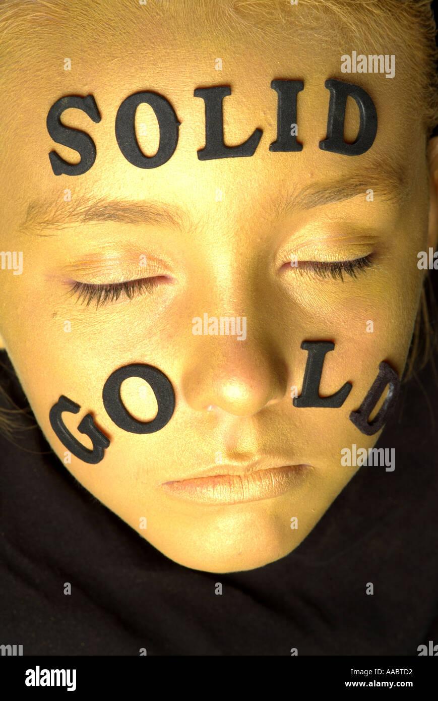 Oro viso della bambina con la scritta in oro massiccio colpo da sopra con gli occhi chiusi Immagini Stock