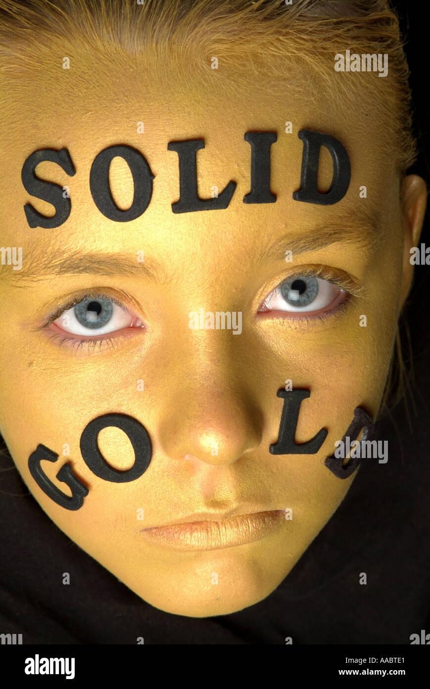 Oro viso della bambina con la scritta in oro massiccio colpo da sopra con gli occhi aperti Immagini Stock