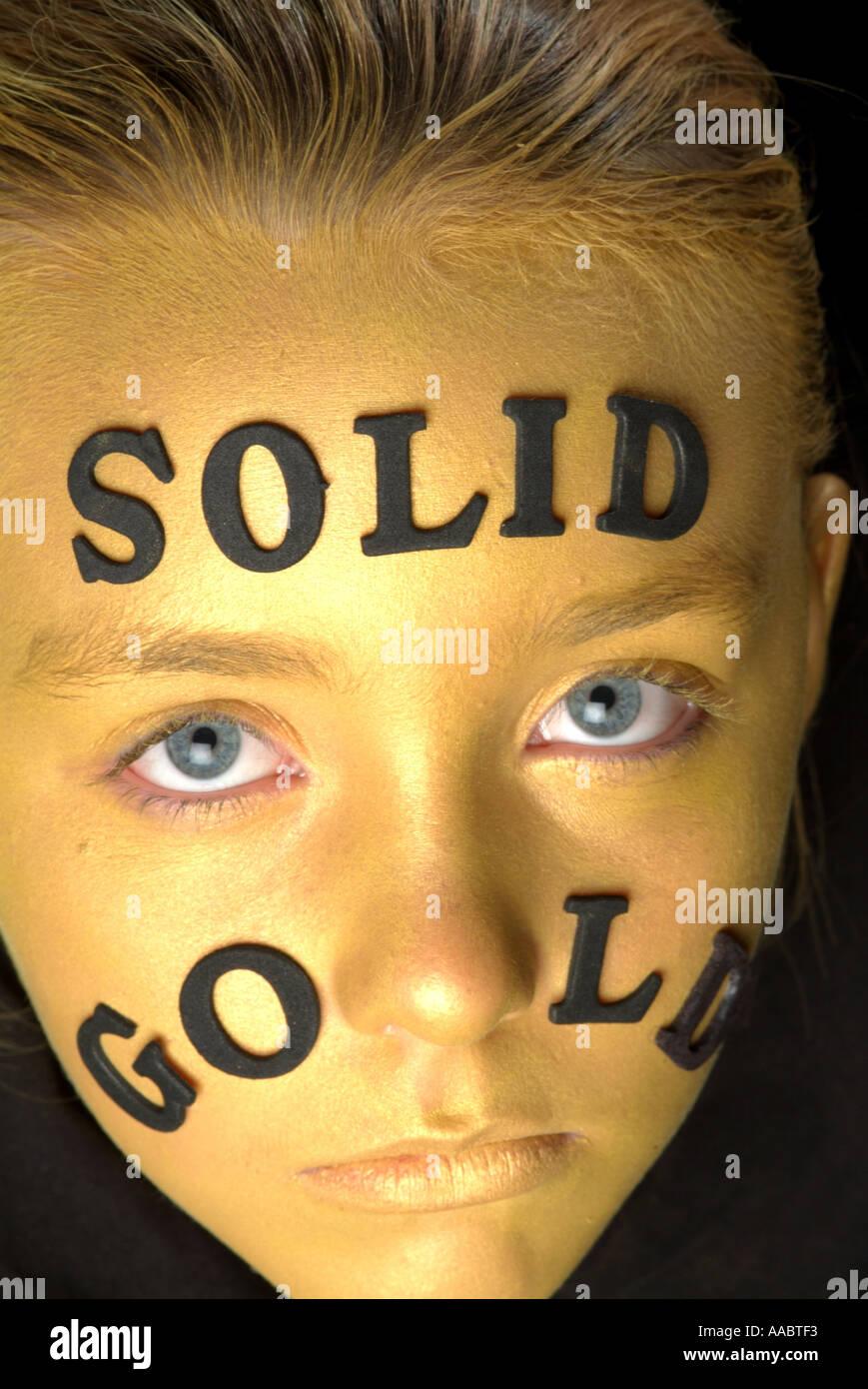 Oro viso della bambina con la scritta in oro massiccio colpo da sopra con gli occhi aperti e un croped mento Immagini Stock