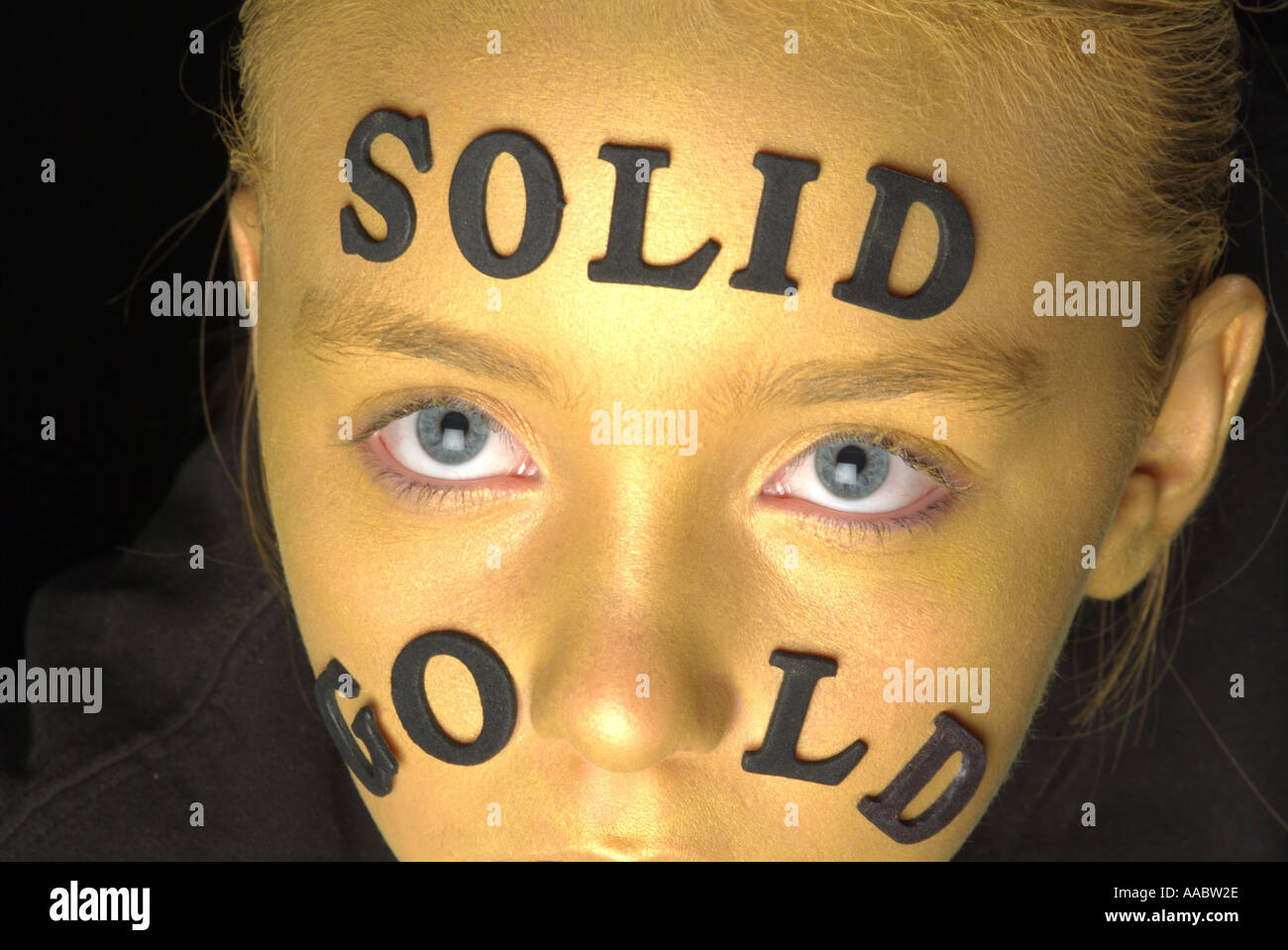 Oro viso della bambina con la scritta in oro massiccio colpo da sopra con gli occhi aperti e un Immagini Stock