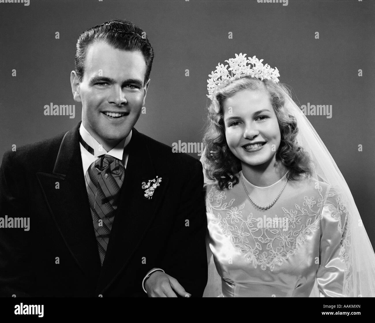 1940s ritratto della sposa e lo sposo legata a braccetto guardando la fotocamera Immagini Stock