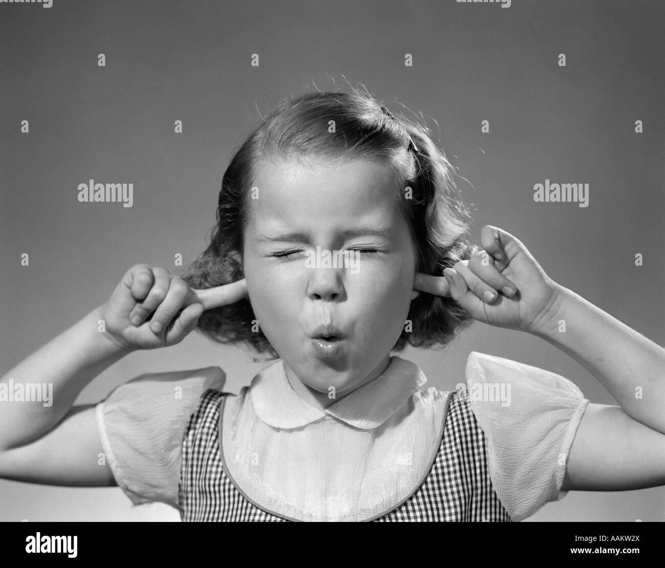 Anni Cinquanta la ragazza con le dita nelle orecchie gli occhi chiusi ascoltando il rumore Immagini Stock