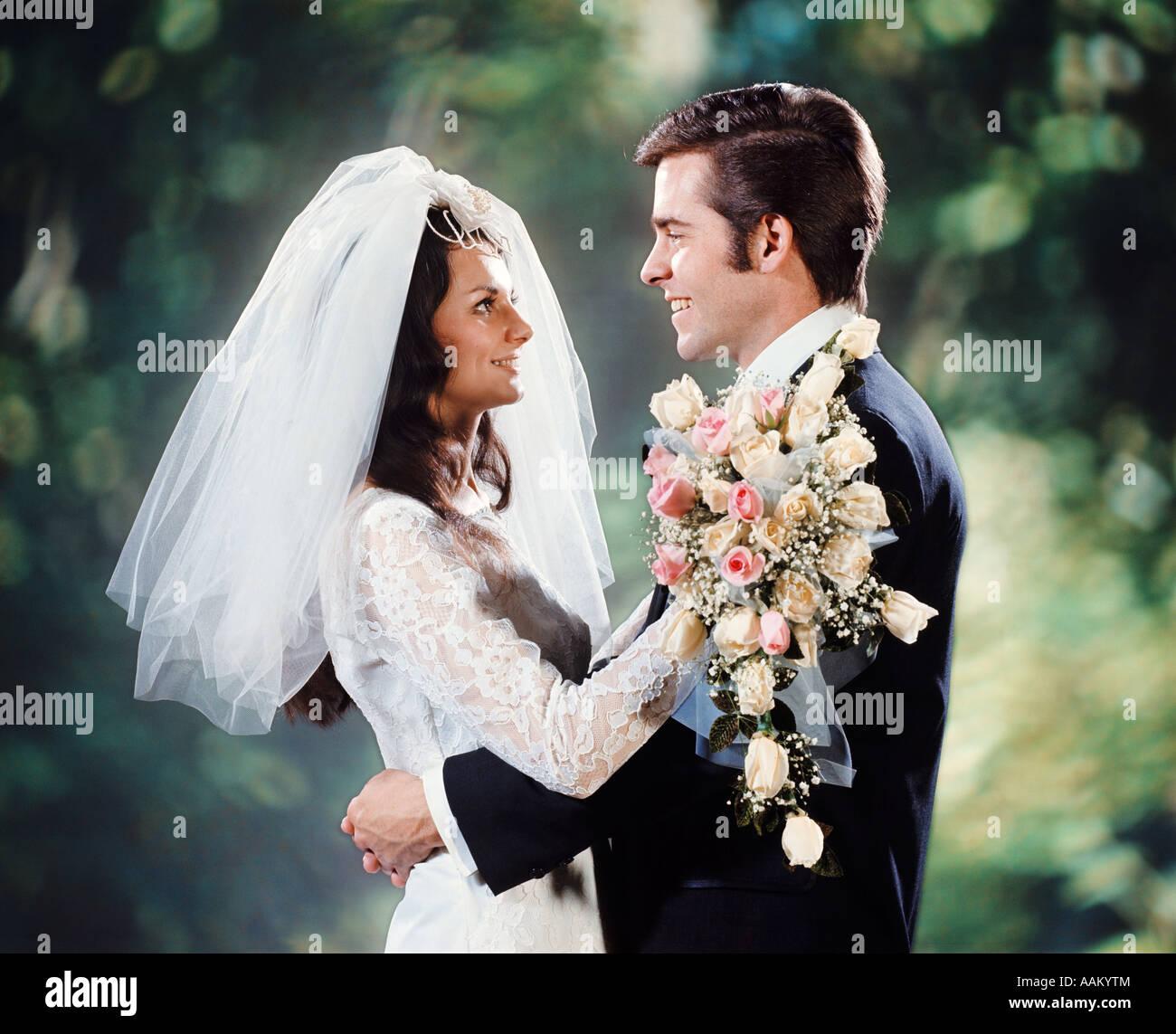Anni Settanta sposa sposo abbracciando abbracciare FACCIA A FACCIA BOUQUET NUZIALE GIOVANE UOMO DONNA Immagini Stock