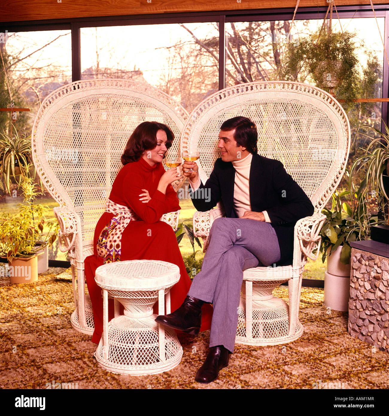 Anni Settanta uomo donna giovane bere il vino sul patio salotto in vimini  bianche sedie di accb3b03e865