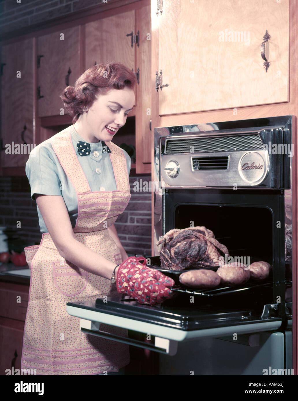 Anni Cinquanta donna sorridente casalinga indossando grembiuli e guanti da  forno tenendo arrosto di vitello al forno con patate al di fuori del forno  di ... a11d81677063