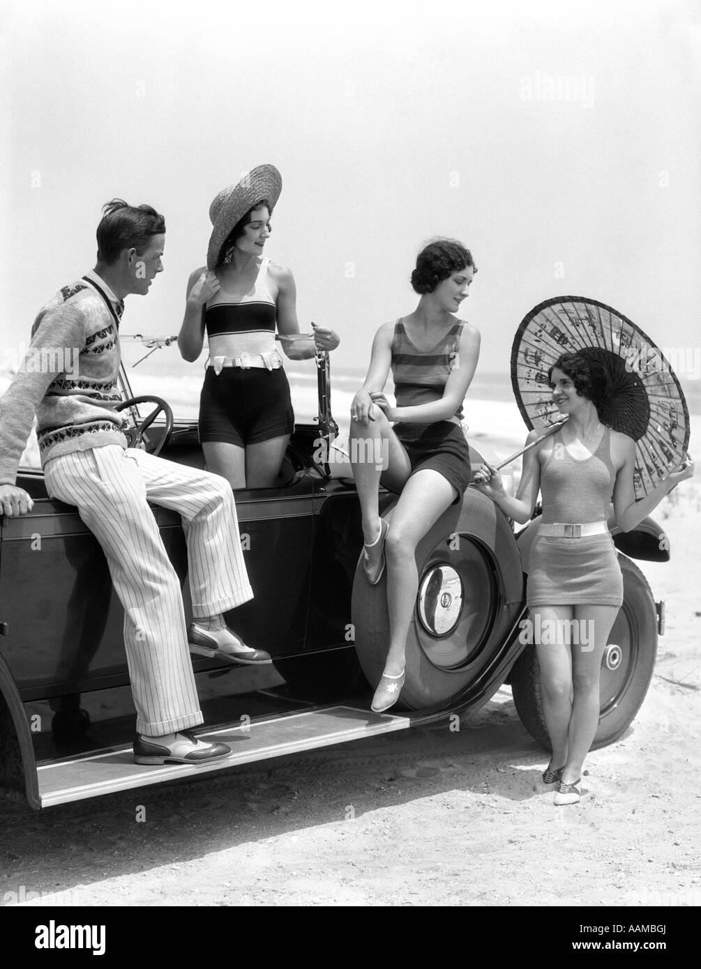 Anni Venti anni trenta uomini E TRE DONNE IN SPIAGGIA vestiti o vestiti bagnantesi in posa con auto sulla scheda Immagini Stock