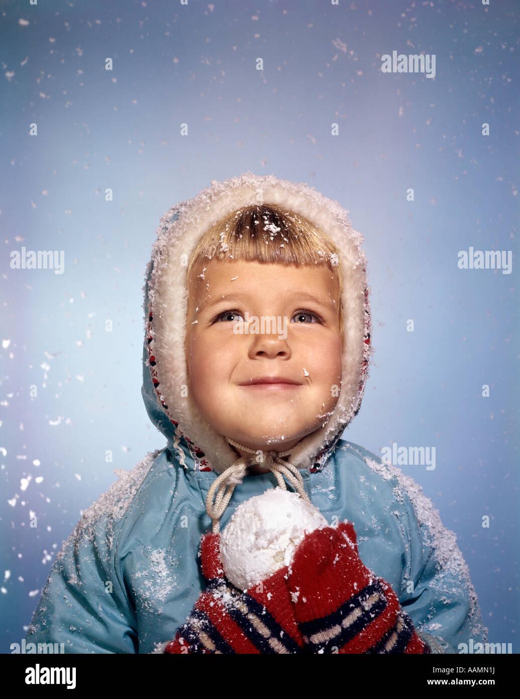 Anni sessanta bambina tenendo palla di neve guardando il cielo rosso sorridente Guanti in maglia bianca cappello Immagini Stock