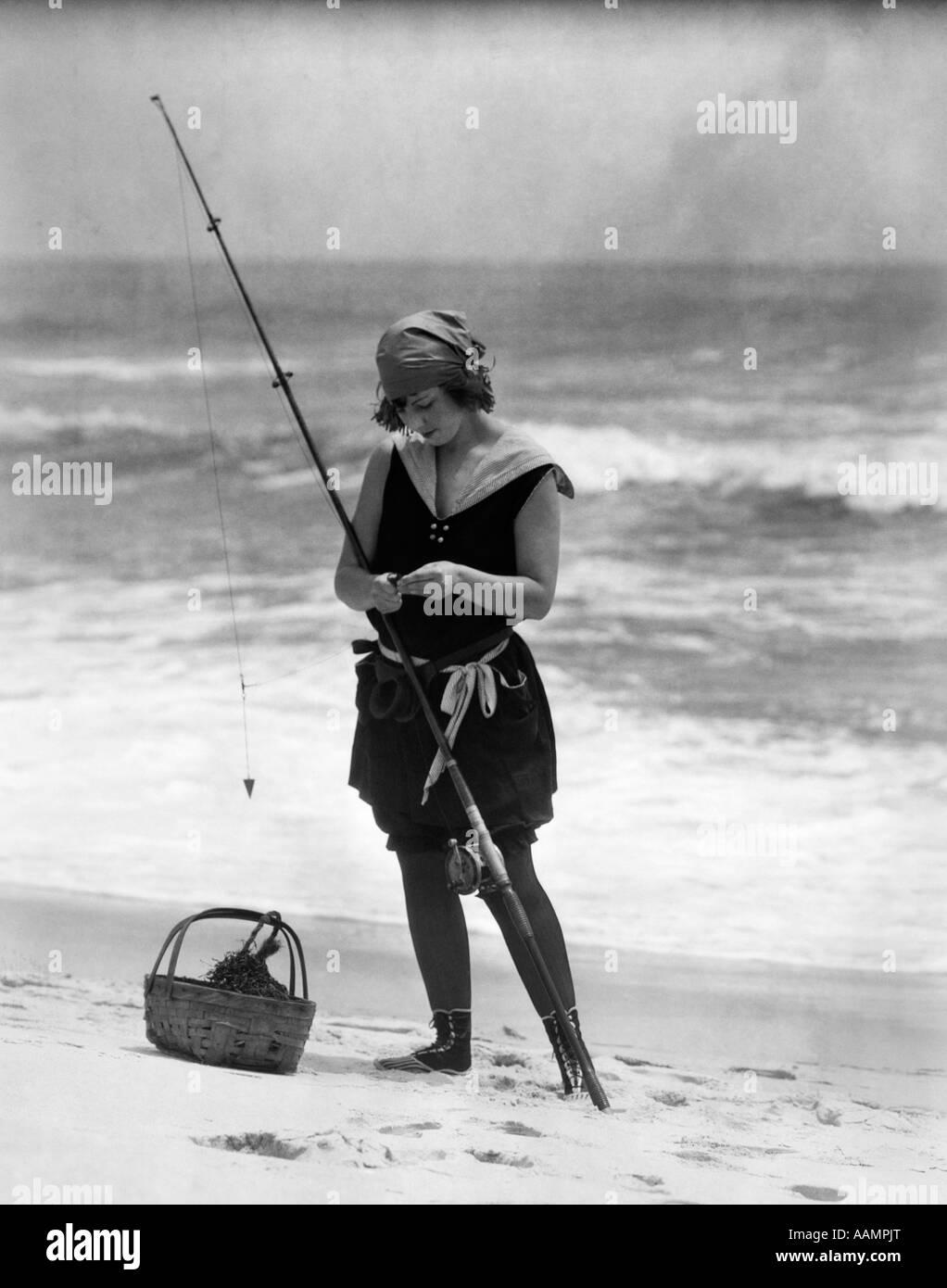 1920s DONNA IN COSTUME DA BAGNO COSTUME PERMANENTE SULLA SPIAGGIA mettendo esca sul surf pesca polo Immagini Stock
