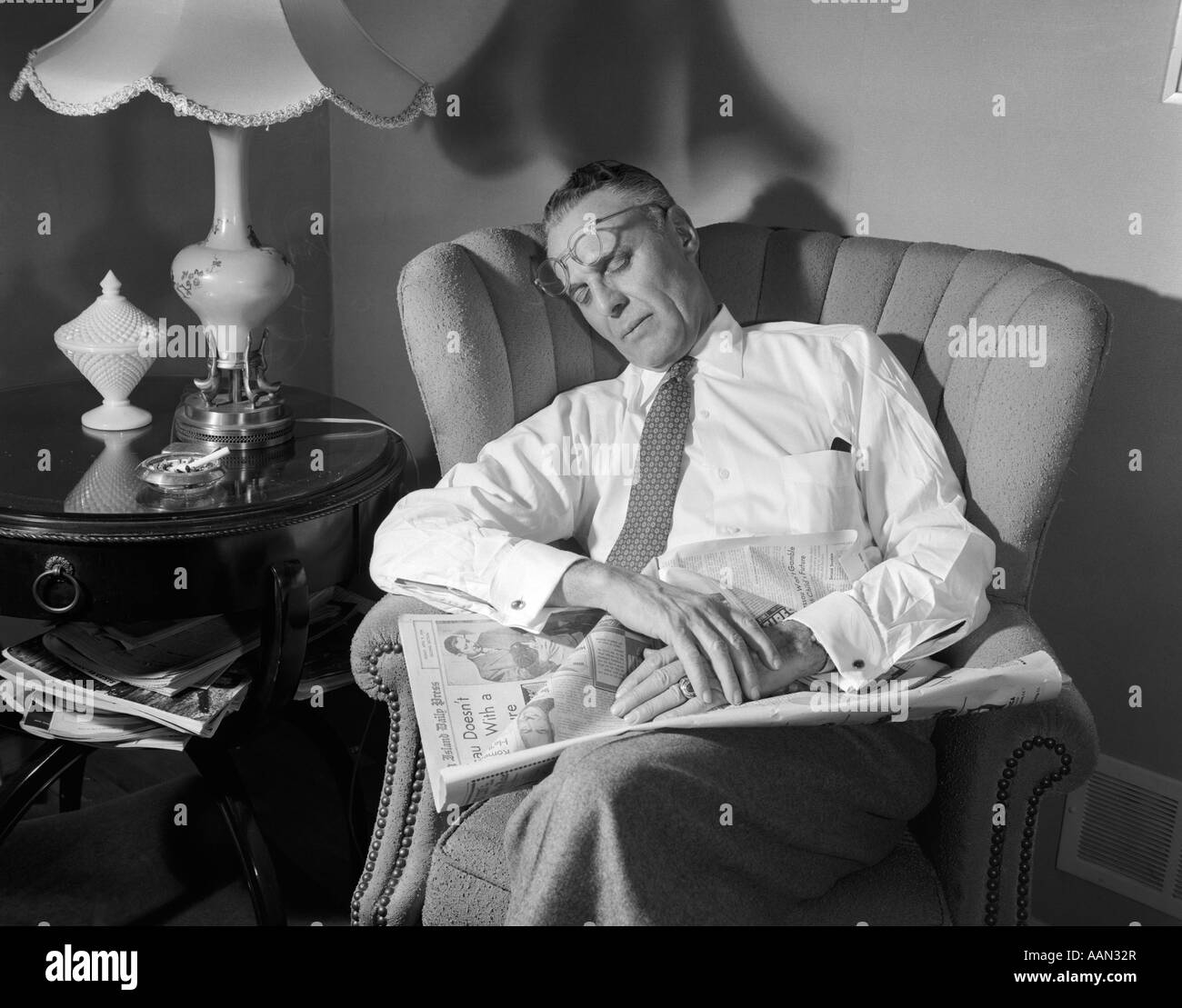 1950s uomo di mezza età addormentato in sedia quotidiano di lettura OCCHIALI spinto sul fronte Immagini Stock