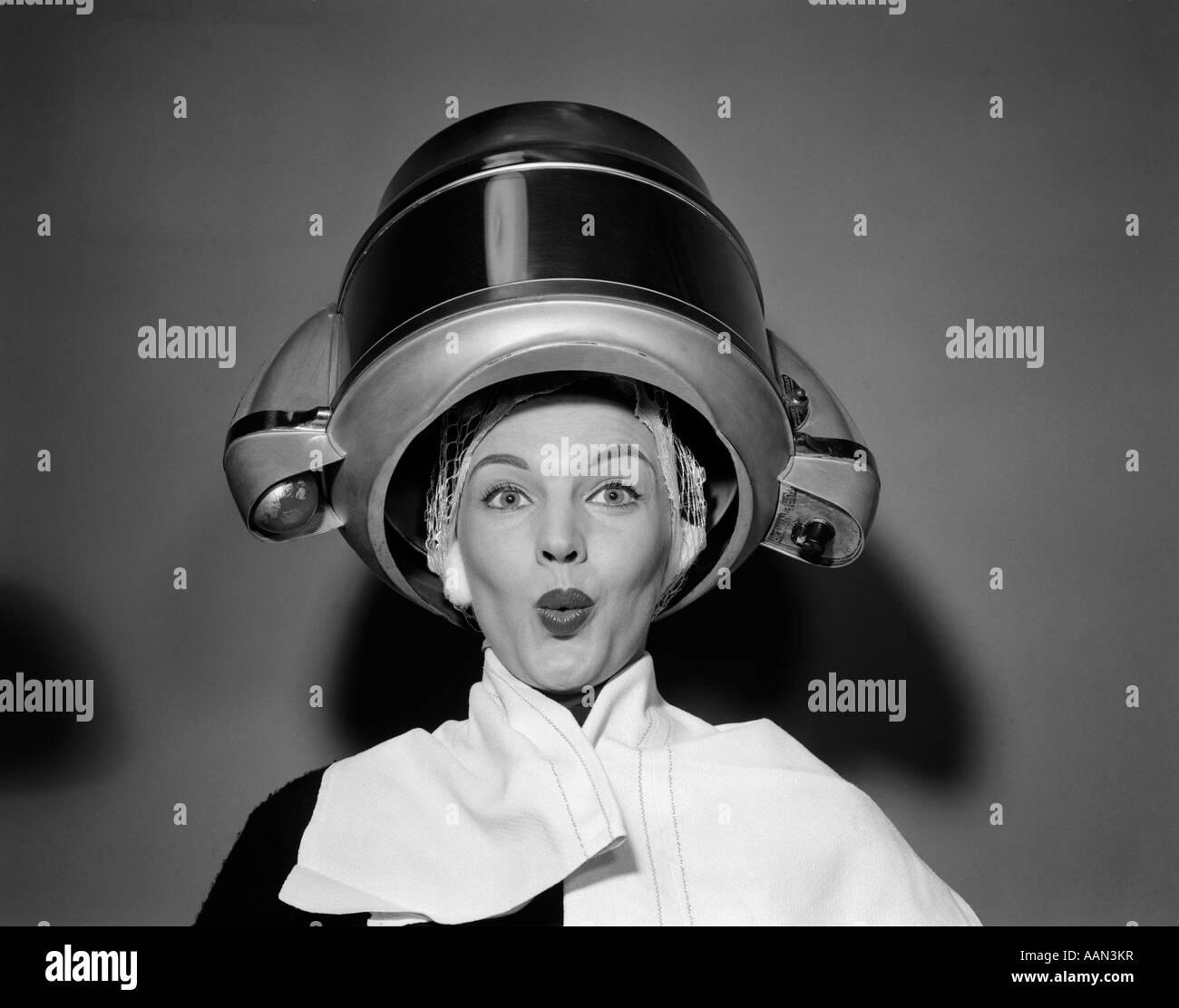 Anni Cinquanta DONNA SOTTO ASCIUGACAPELLI con asciugamano sulle spalle e la retina per capelli guardando la fotocamera Immagini Stock