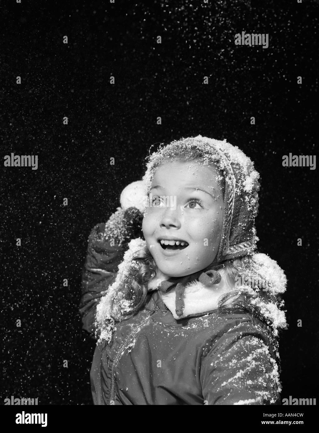 Anni Cinquanta bambina con finti fiocchi di neve caduta sul cappello e  capelli lanciando palle di neve IN STUDIO e652eaaf358f