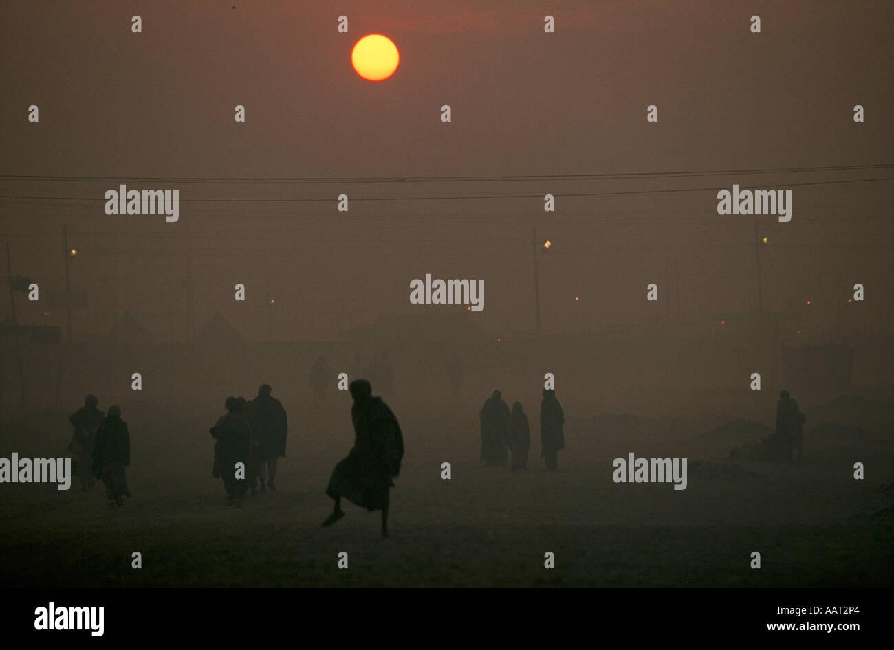 KUMBH MELA INDIA 2001 come il sole tramonta il fumo di fuochi di legno crea una spessa smog pellegrini tornare nei loro campi 2001 Foto Stock