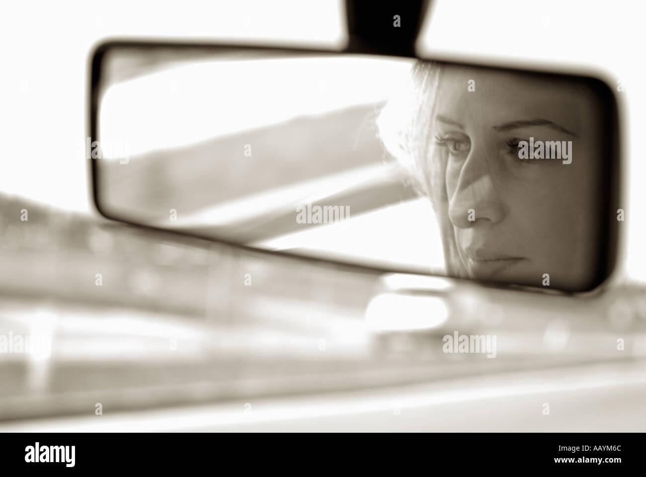 Donna in specchietto retrovisore di un auto guidando su una strada Foto Stock
