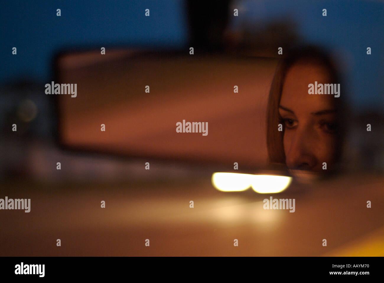 Specchio retrovisore con la riflessione di un volto di donna in un auto guidando lungo una strada di notte Immagini Stock