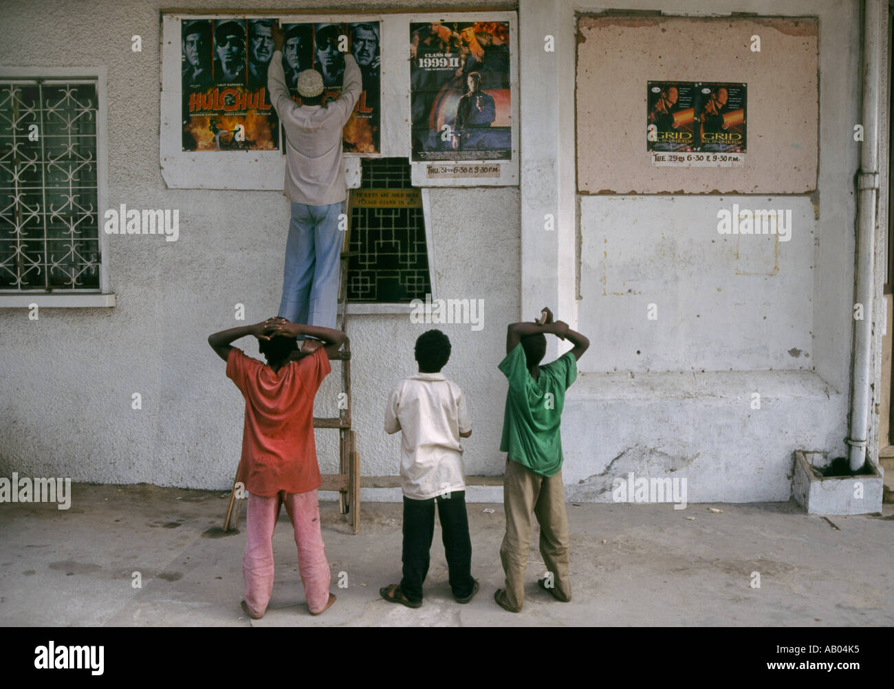 Zanzibari ragazzi guardare un poster per un film che viene messo in un cinema della città di pietra Luglio 1997 Immagini Stock