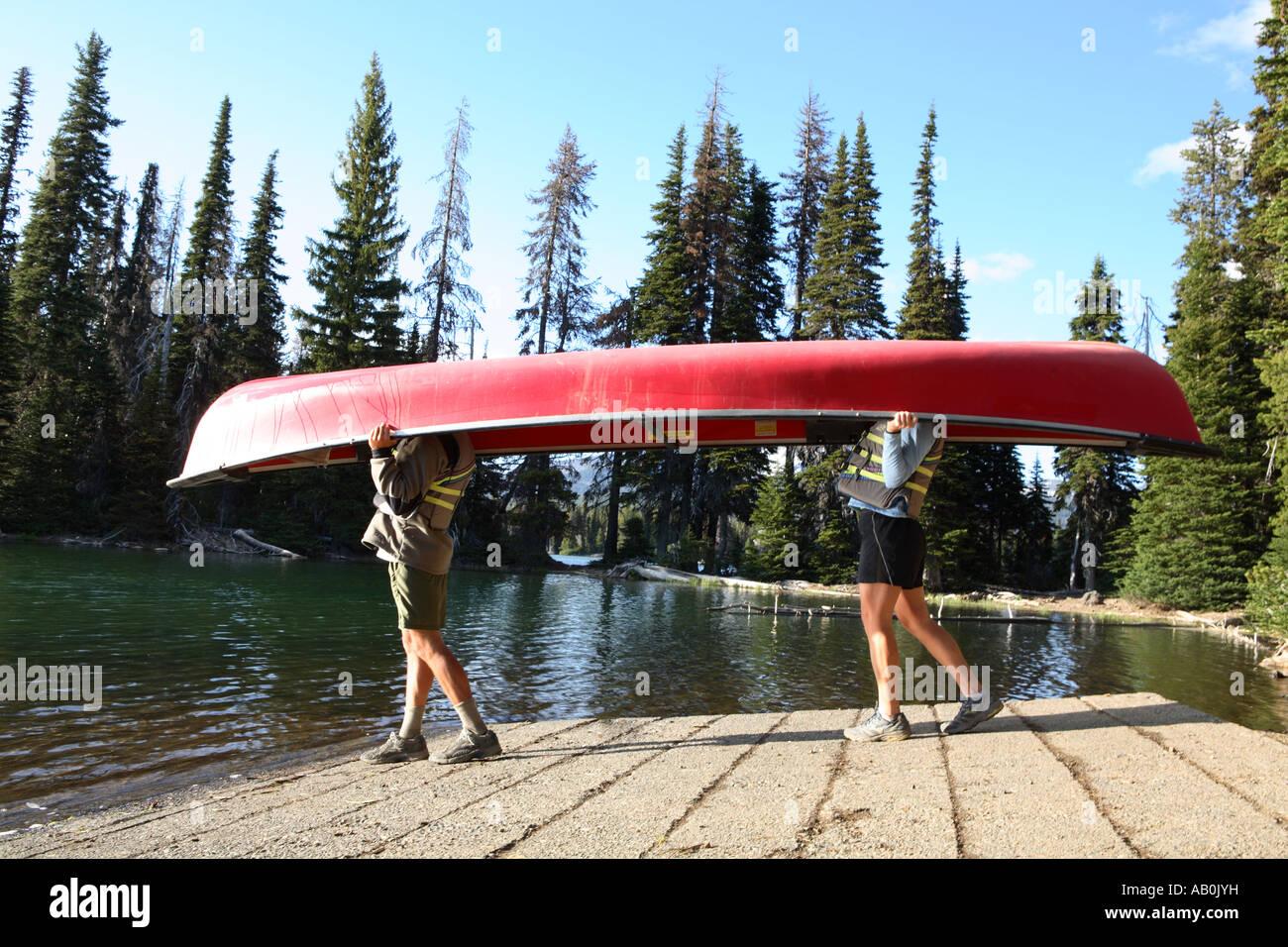 Giovane passeggiate al lago con una canoa sopra le loro teste Immagini Stock