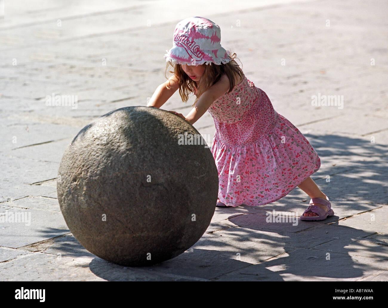 Una giovane ragazza spingendo una grande palla di cannone Immagini Stock