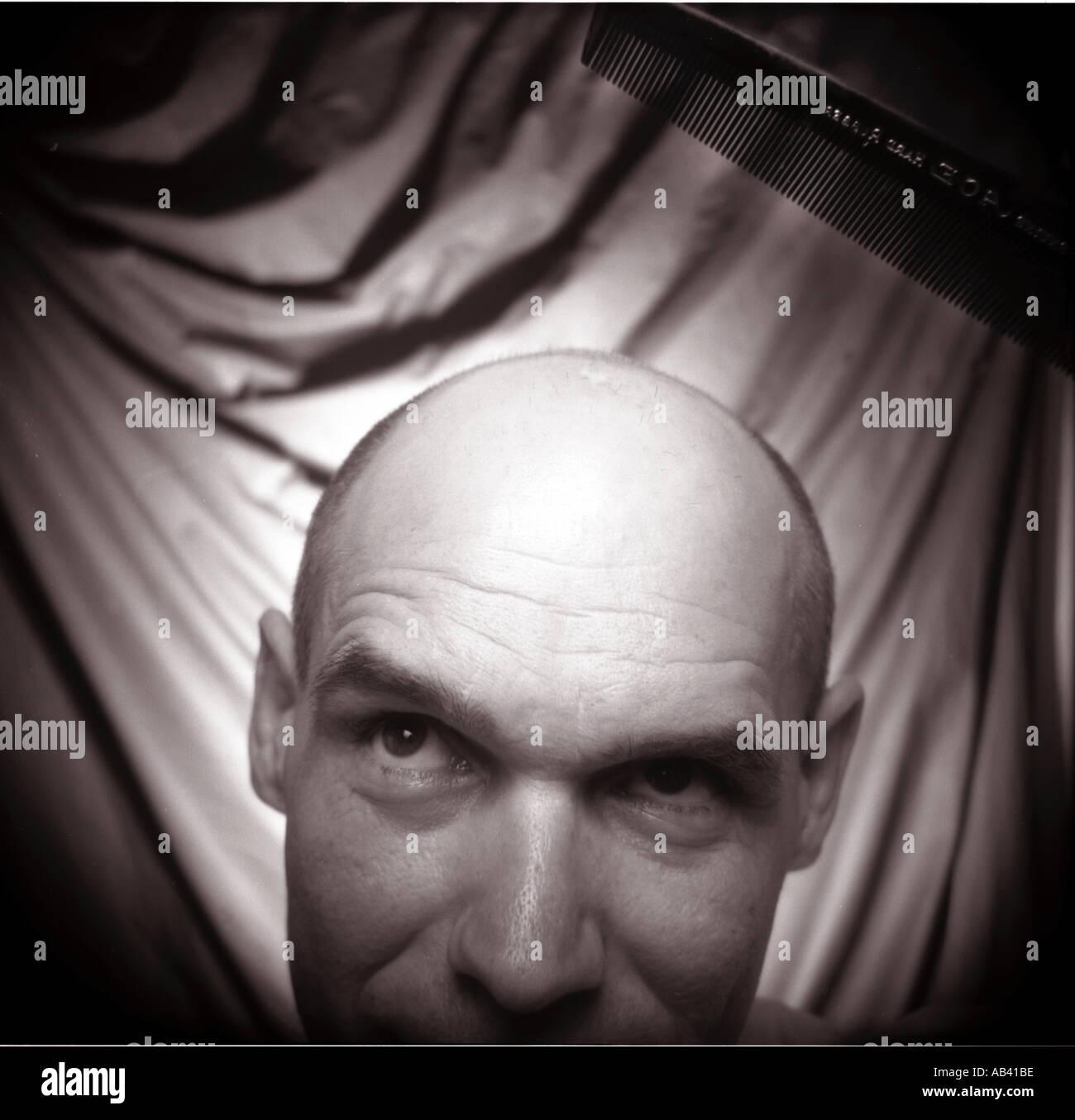 Uomo calvo la pettinatura della sua ultima ciocca di capelli umorismo Immagini Stock