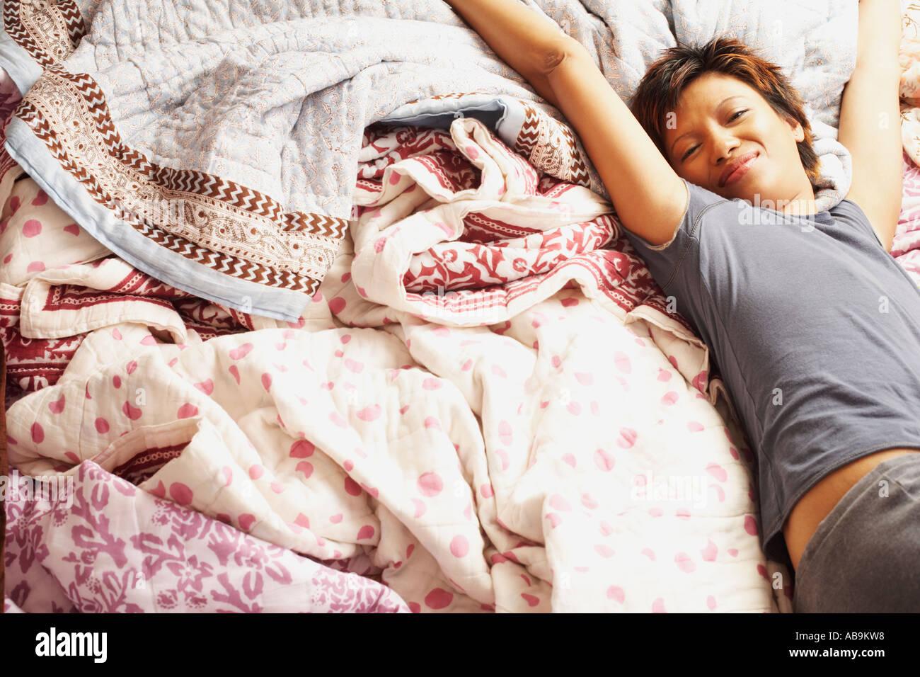 Giovane donna stretching nel letto Foto Stock