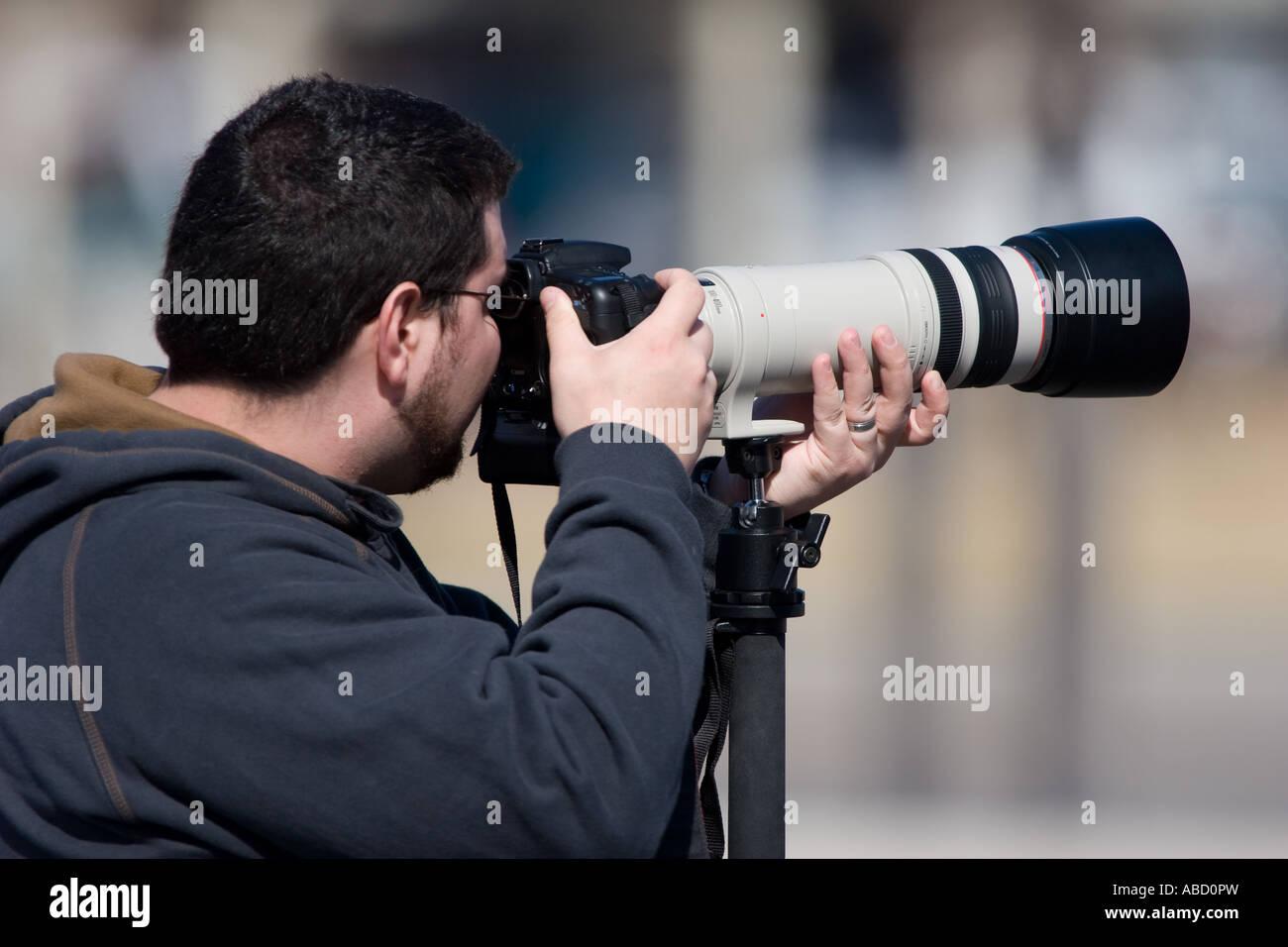 Un fotografo può contenere fino a un canonico 100-400L un teleobiettivo su un EOS 20D fotocamera. Immagini Stock