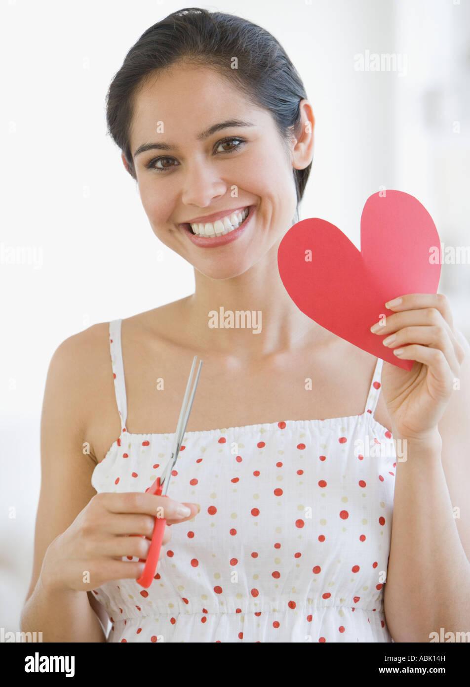 Donna che mantiene tagliare fuori il cuore della carta Foto Stock