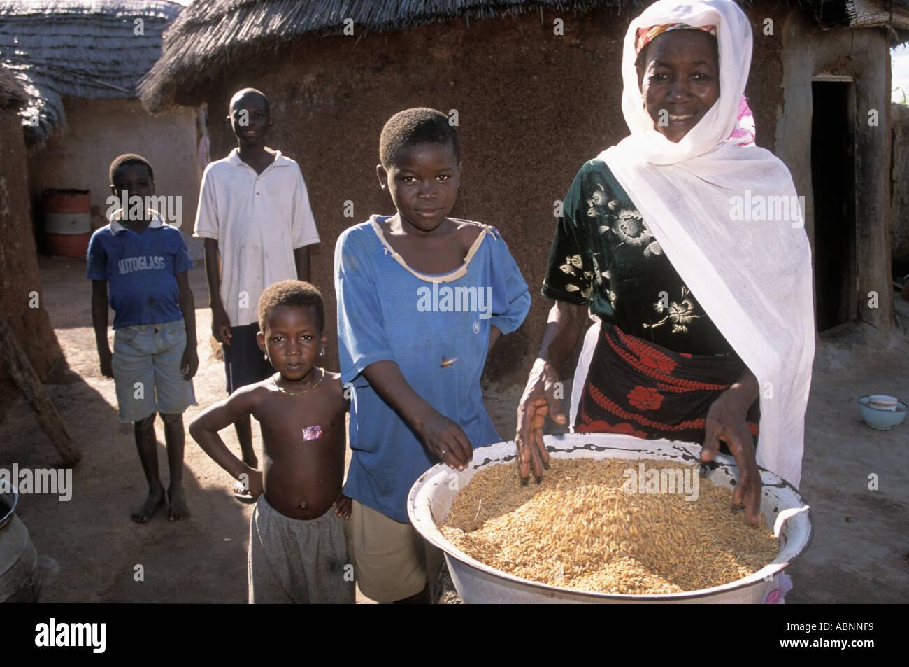 Donna del Ghana dimostra la sua ciotola di riso come tutti gli agricoltori locali è vittima di ingiustizie del commercio mondiale appelli per il commercio equo e solidale Immagini Stock