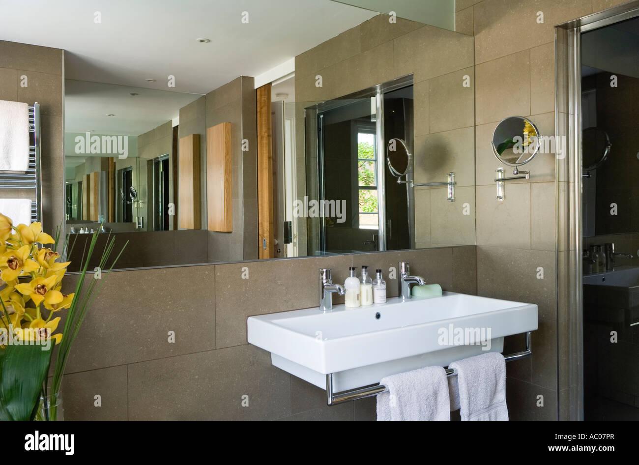 Lavandino in bagno modernista con un grande specchio e piastrelle