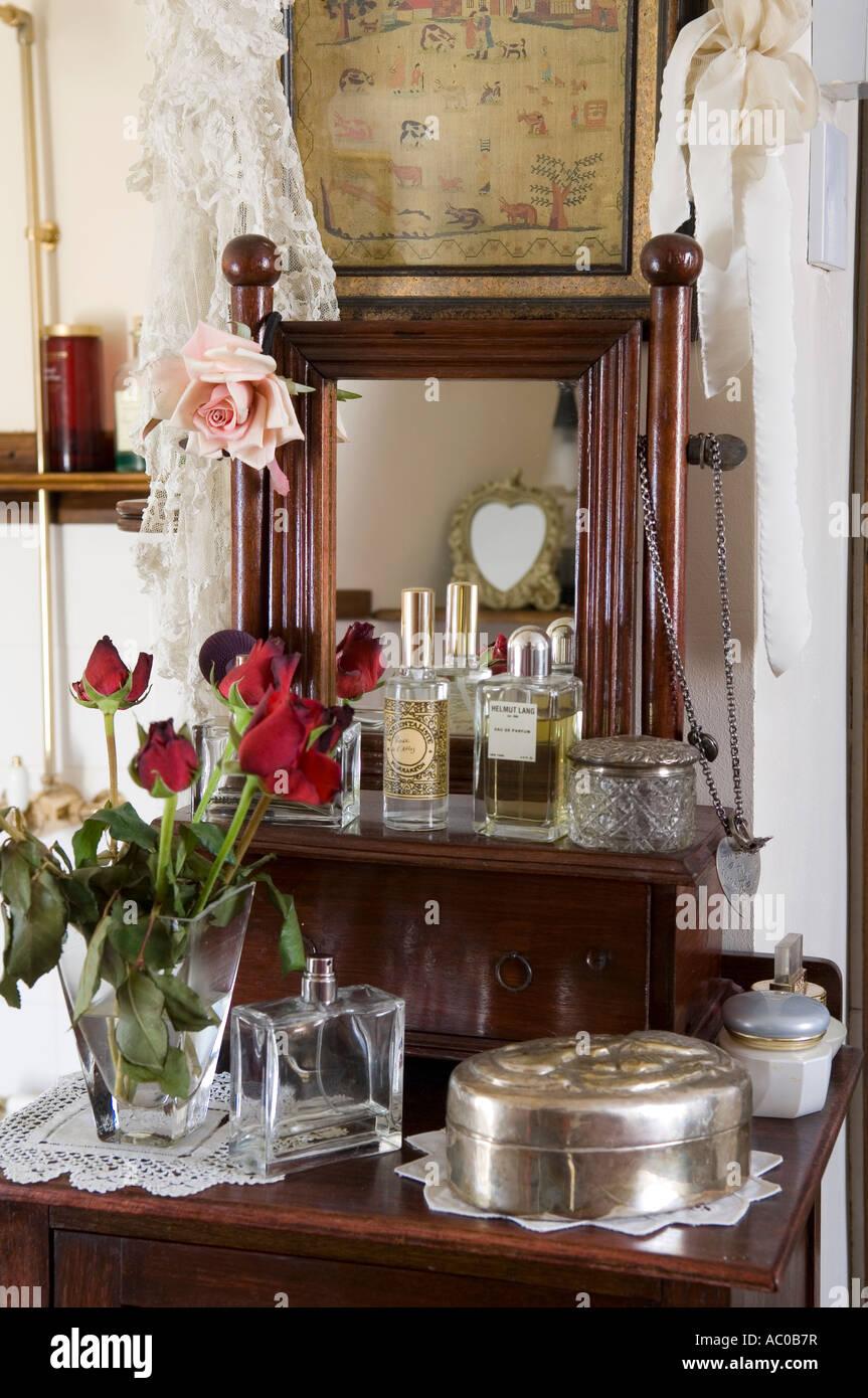 Rose rosse sul tavolo della toeletta con vecchie bottiglie di profumo Immagini Stock