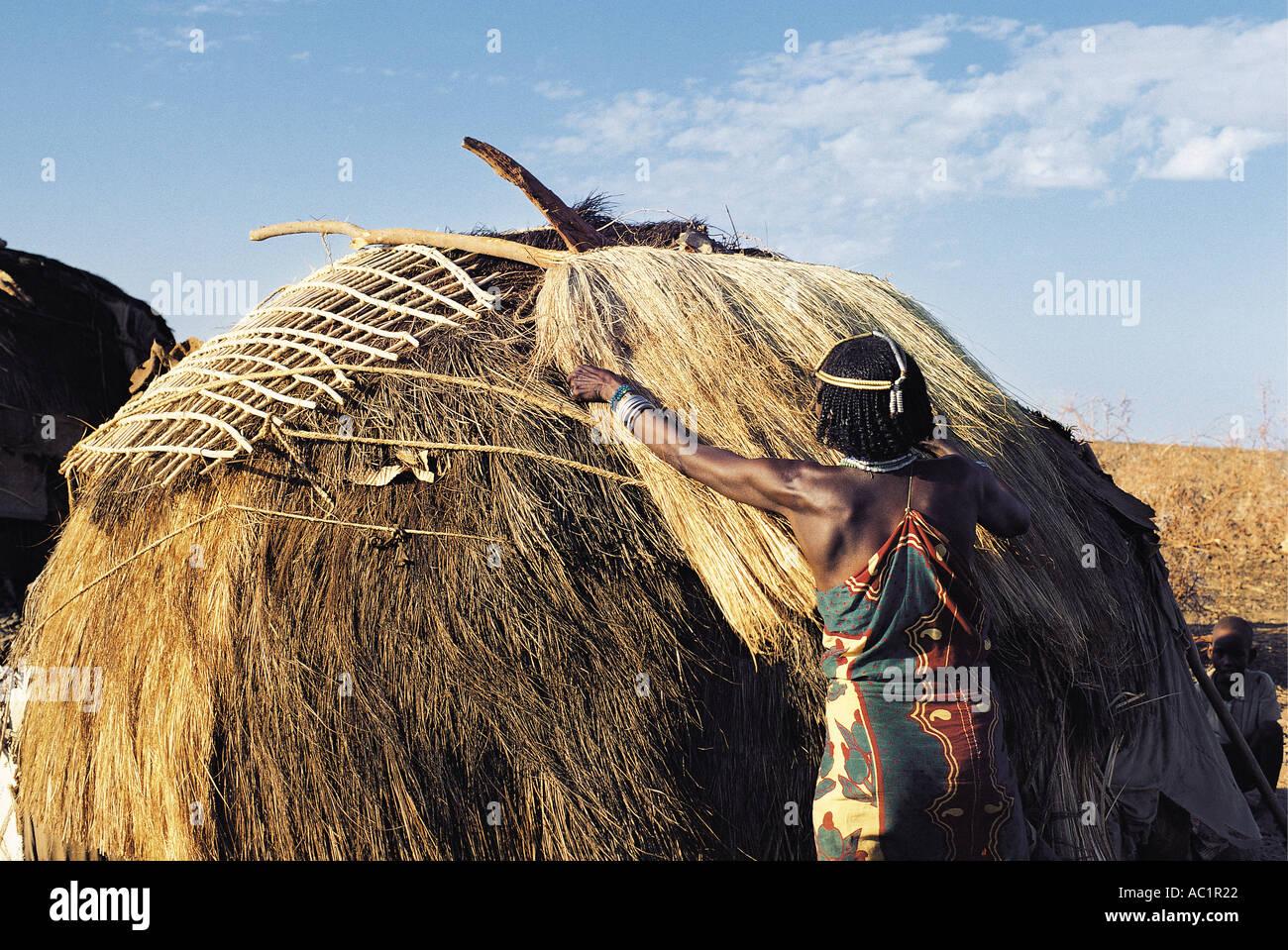 Gabbra donna sposata collocando un tappetino di sisal che lei ha appena finito di tessitura sul tetto del suo rifugio Immagini Stock