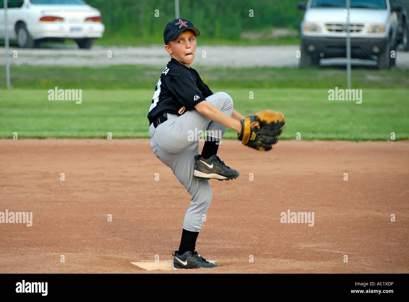 Little League Baseball pitcher player gettando un baseball Immagini Stock