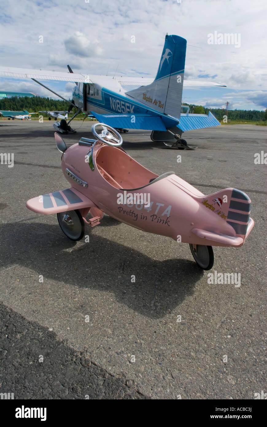 Rosa giocattolo per bambini è aereo accanto a un Cessna 185