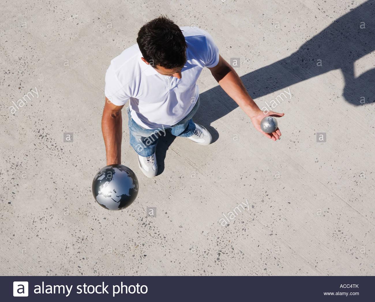 Vista aerea dell'uomo tenere grandi e piccoli globi all'aperto Immagini Stock