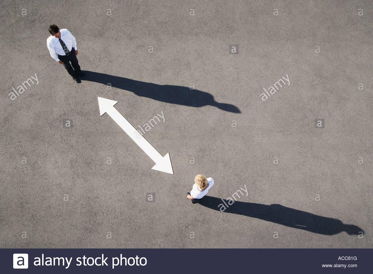 Vista aerea di un uomo e di una donna con la freccia sulla pavimentazione Immagini Stock