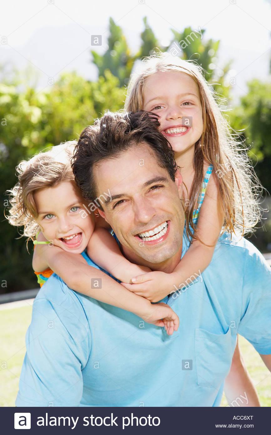 Un padre con le sue due giovani figlie sollevato sulla sua schiena Immagini Stock