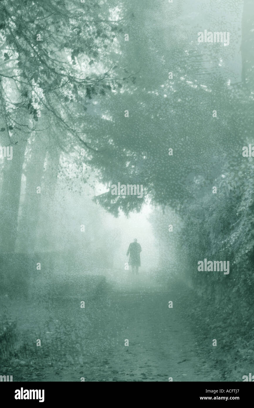 Foto di un uomo a piedi giù per un sentiero nella nebbia Immagini Stock