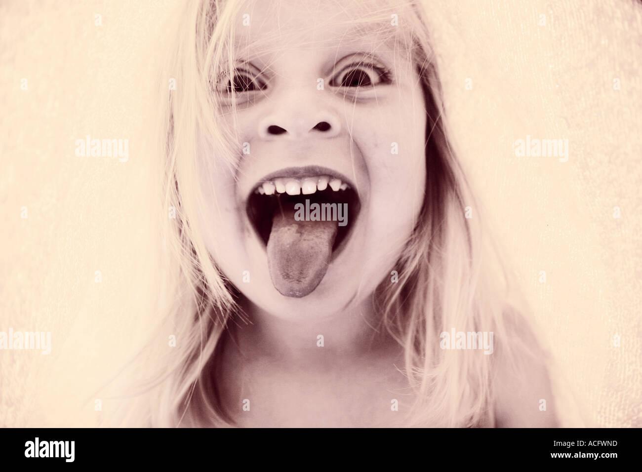 Foto di un bambino il suo incollaggio con la lingua fuori Immagini Stock