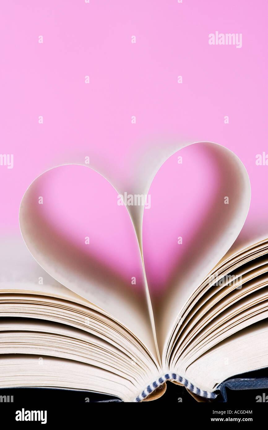Forma di cuore costituito da pagine di libri contro un sfondo rosa Immagini Stock