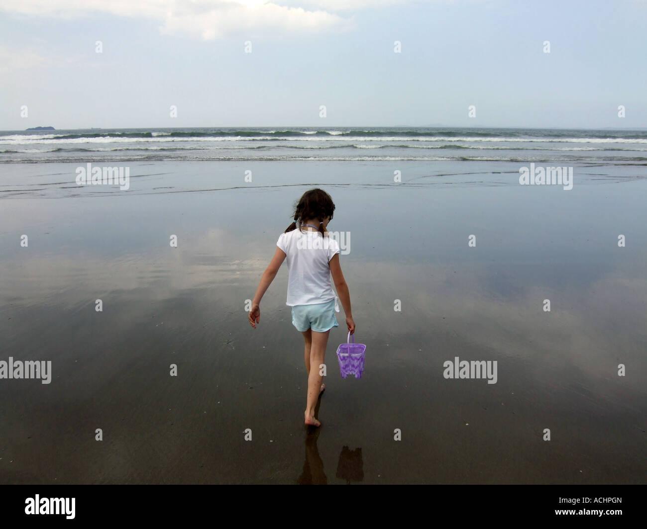 Ragazza camminare verso il mare portante una benna, REGNO UNITO Foto Stock