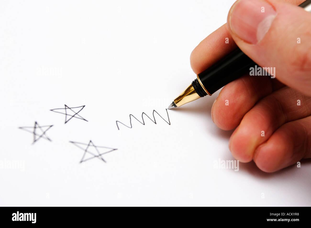 Una mano d'uomo progettazione stelle e uno scarabocchio con una penna nera Immagini Stock