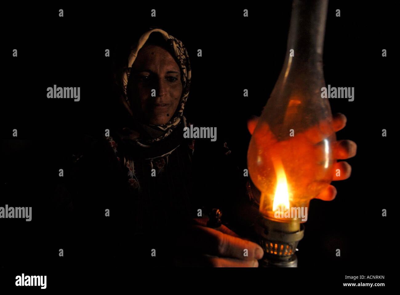 Una donna Palestinese accensione di una lampada di kerosene in una grotta abitata in Al Mufaqarah borgo situato Immagini Stock