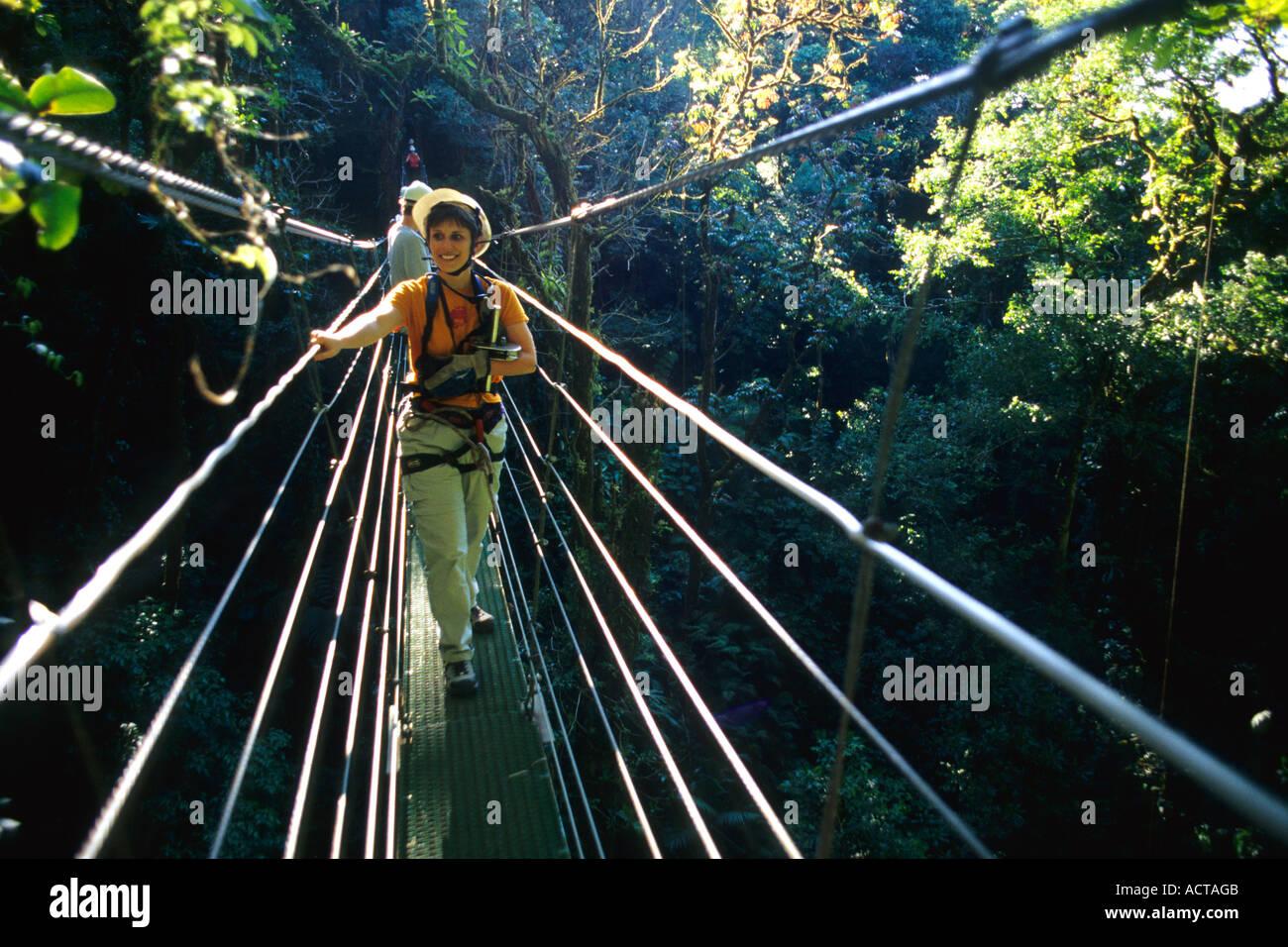 Donna sul ponte del cavo attraverso la foresta pluviale, Monteverde in Costa Rica Immagini Stock