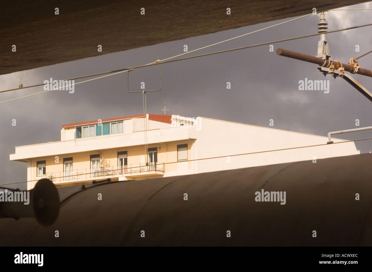 Soleggiato appartamento in Messina Sicilia dalla stazione ferroviaria sopra la parte superiore del tetto del treno e al di sotto del massimale della piattaforma del treno Immagini Stock