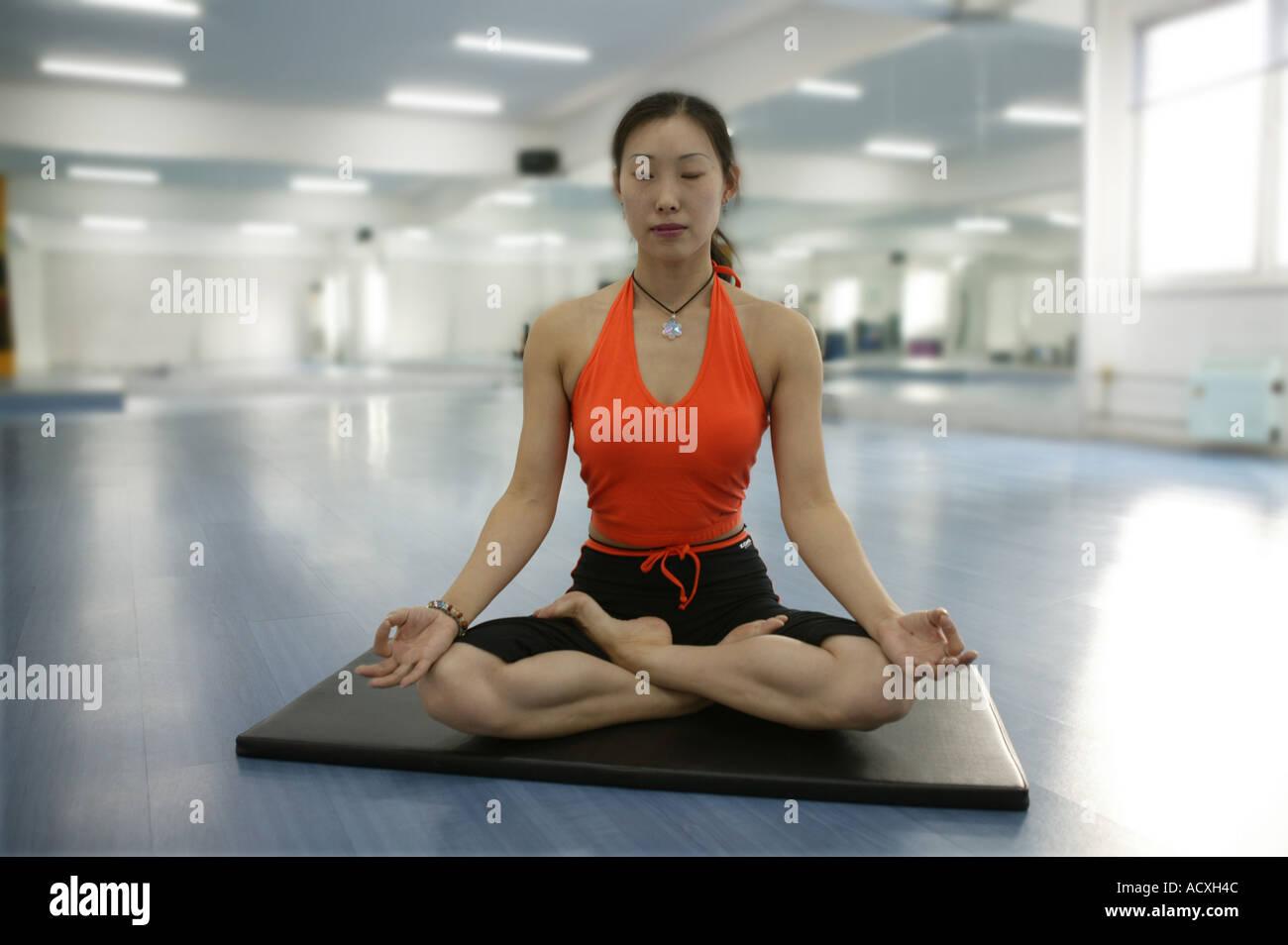 Un giovane cinese donna siiting con le gambe incrociate gli occhi chiusi Immagini Stock